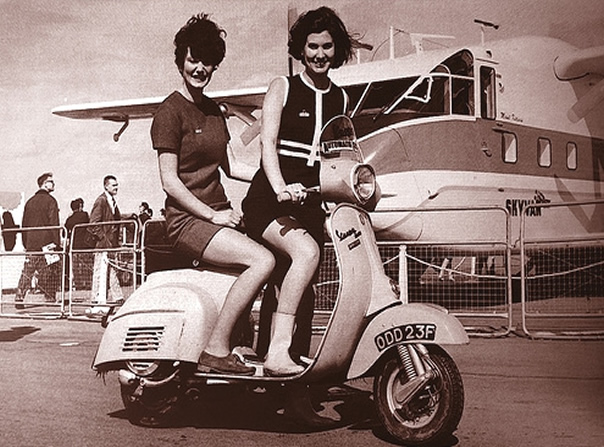 2 stewardess riding a scooter